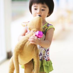 young asian girl at school with her reindeer soft toy