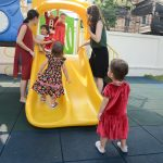 children playing on outdoor play slide at nursery