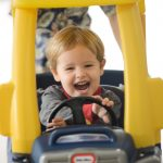 young boy in tiny tikes car