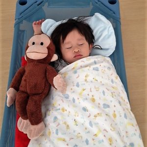 young boy with monkey toy during school nap time Ekamai