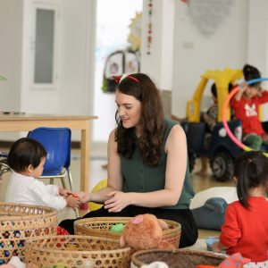 baby passing toys to a kindergarten teacher