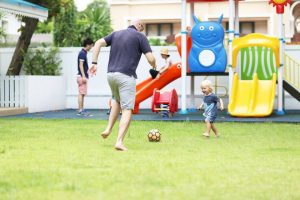 toddler and dad kicking a ball about at play group in the Bangkok heat.