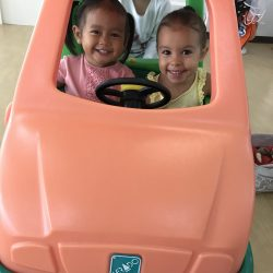 Happy young girls role playing the school bus at Bright Skies internmational pre-school