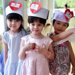 three little girls with love heart hats
