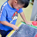 young boy drawing love hearts on a chalk board