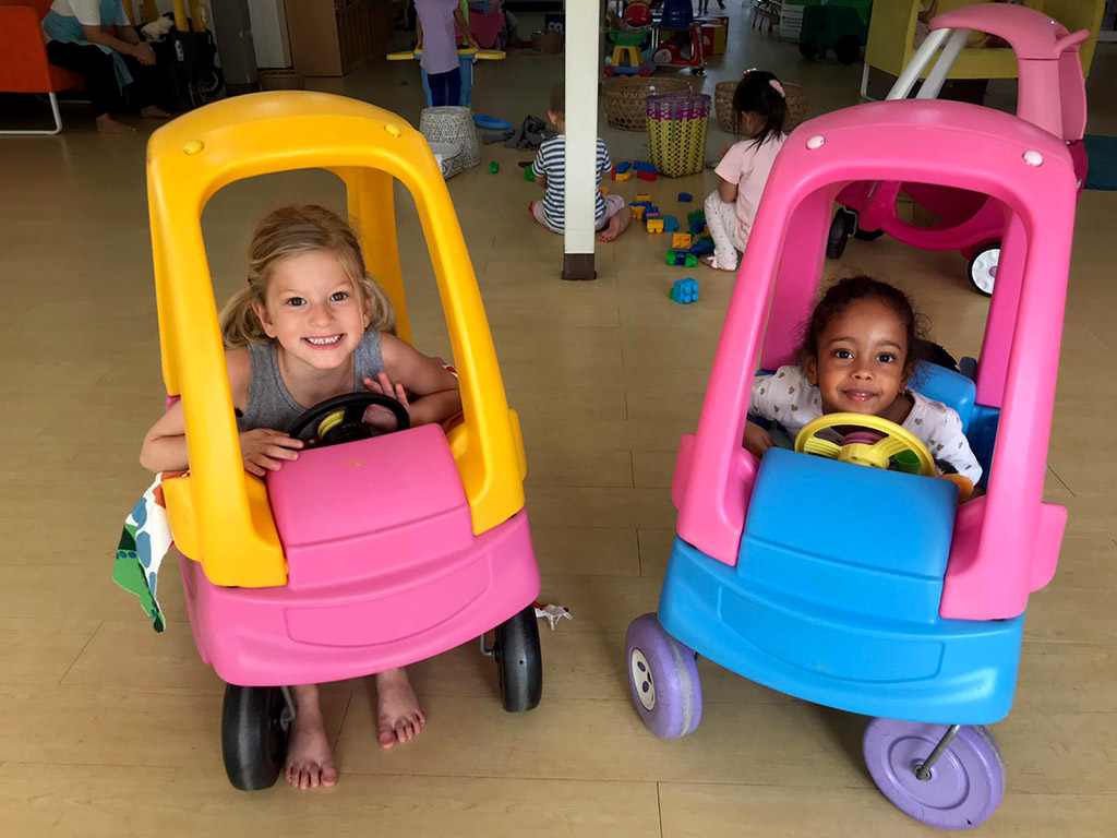 girls in toy cars at pre-school