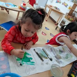 nursery children painting in the classroom at Bright Skies School Bangkok