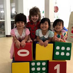 children playing with over sized colourful building blocks